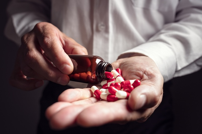 Pouring prescription drugs capsules from a pill bottle into hand